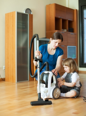 teaches: Woman teaches baby girl to use the vacuum cleaner in living room