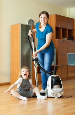 Family chores with vacuum cleaner on parquet photo