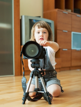 2 years child takes photo with camera and tripod photo