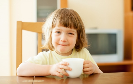 2 years child drinking from cup in home photo