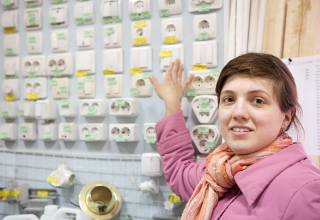 Young woman chooses  switch in  electrical store Stock Photo - 19270069