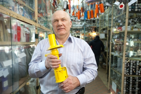 decelerator: mature man holds  shock absorber  in  auto parts store Stock Photo
