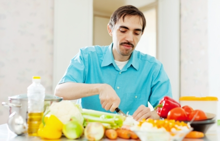 Caucasian man cooking dinner with vegetables at home kitchen photo