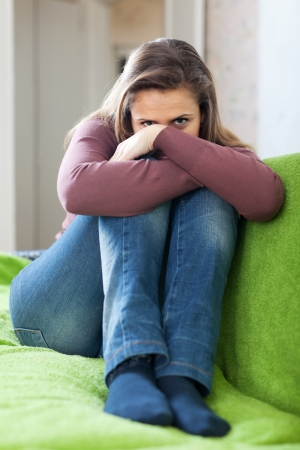 Lonely girl sitting on the sofa at  home Stock Photo - 19341707