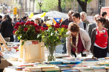 BARCELONA, SPAIN - APRIL 23: Books and roses on street stalls in April 23, 2013 in Barcelona, Spain. Widely celebrated in Barcelona, ​​decided to give red roses and books