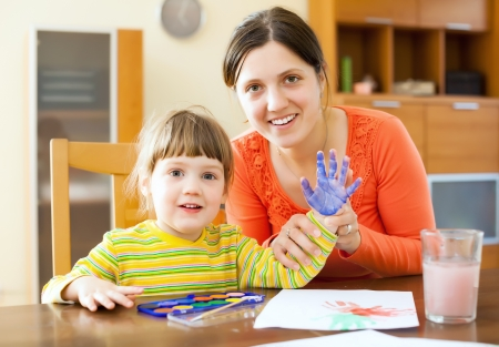 fingerprinting: Happy mother and her child painting on paper with handprinting