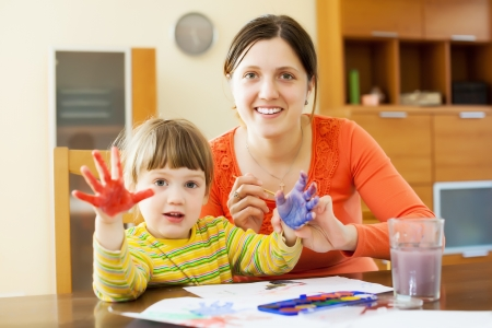 fingerprinting: Happy mother and her child drawing on paper with hand printing