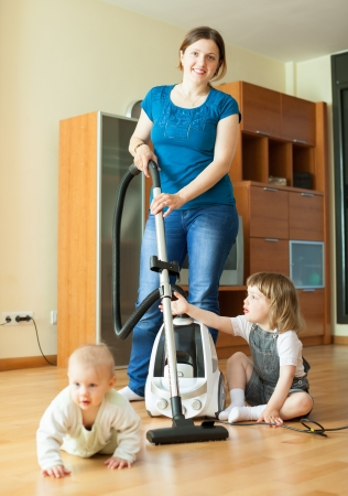 Happy mother wth two children cleans living room with vacuum cleaner  photo