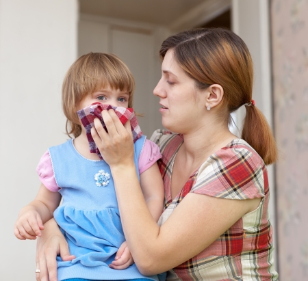 catarrh: woman wipes snot her child at home Stock Photo