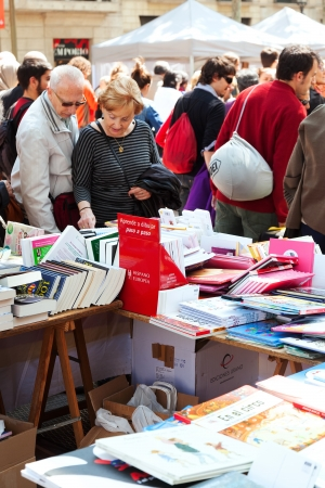 BARCELONA, CATALONIA - APRIL 23: Books on street stalls in April 23, 2013 in Barcelona, Catalonia.Books and  roses - symbols of Sant Jordi feast in Catalunia