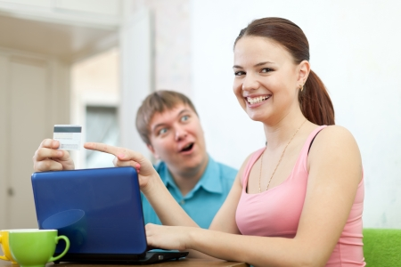 happy couple doing shopping in internet with credit card at home photo