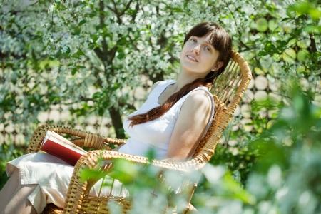 Girl reading book in bloom garden photo