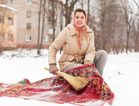 Young woman cleans red rug with snow in winter day outdoor photo