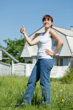 Happy young woman standing on lawn in front of new home Stock Photo - 20388485