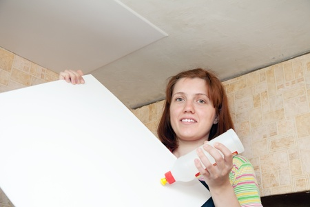 remount: Girl glues ceiling tile at home