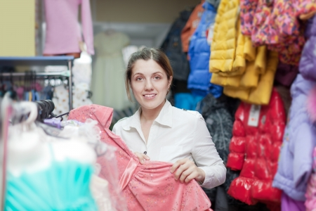 female buyer chooses dress at clothing store photo