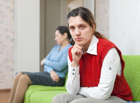 Young woman and mother after quarrel at home photo