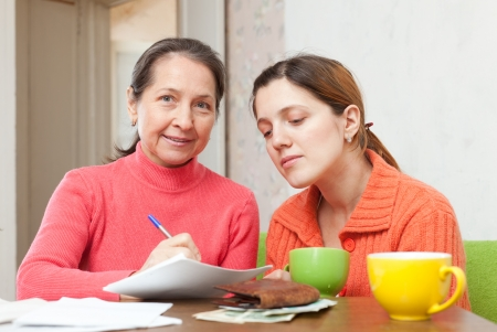 Two  women fills in utility payments bills at  home. Focus on mature photo