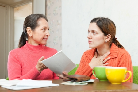 utility payments: Mature mother berates adult daughter for utility payments bills or credits at home Stock Photo