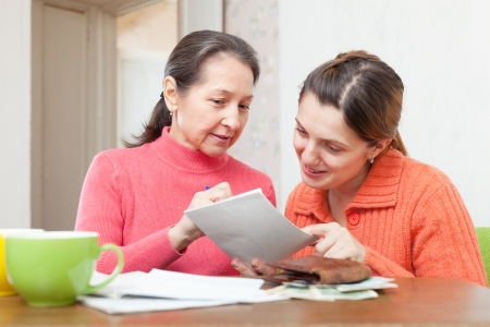 Two positive women fills in payments bills at  home Stock Photo - 19401621