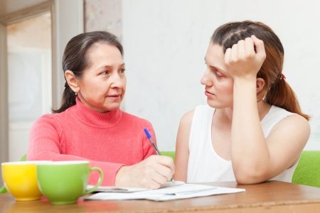 parsimony: Adult daughter with mature mother  fills in the documents at  home Stock Photo