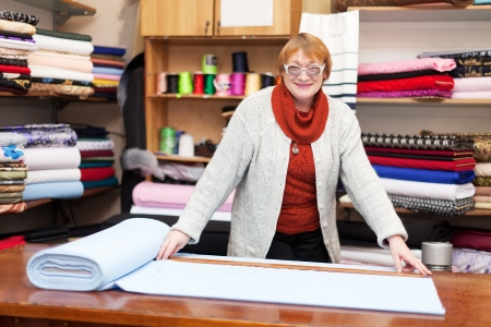 store keeper: Mature salesclerk measures the fabric in a fabric shop
