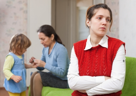Conflict between generations. Sad young woman against mother and daughter at home Stock Photo - 19405820