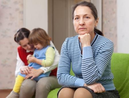 conflictos sociales: El conflicto de las generaciones. Mujer triste contra la hija con el beb� en casa