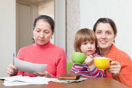 Family of three  generation  fills in utility payments bills at home Stock Photo - 19405816