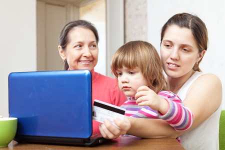 Two women and child with laptop, paying by credit card in internet store  photo