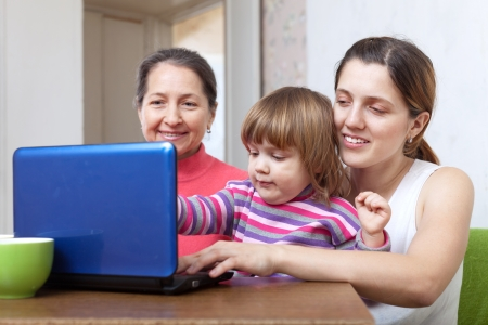 three generations of women: Women of three generations with netbook on sofa in living room