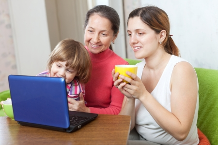 three generations of women: Happy women  of three generations with netbook on sofa in living room