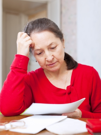utility payments: Sadness mature woman with bills at her home