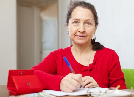 lamentable: serious mature woman fills utility bills at her home