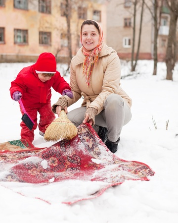 Smiling mother with daughter cleans rug with snow in winter day  photo