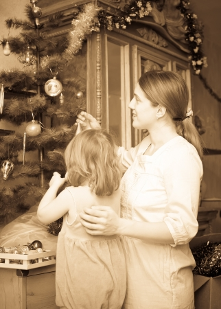 mother and child preparing for  Christmas at home. Imitation of an old image photo