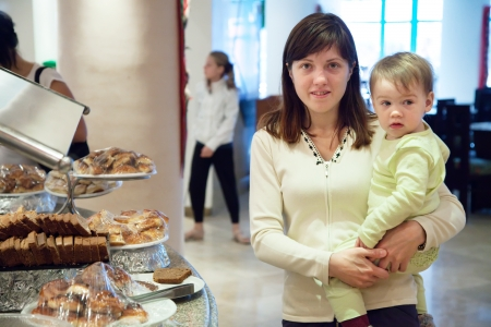 mother with child  near sweet pastry in buffet at hotel photo