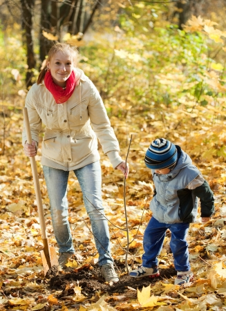 young woman with her son planting  tree in autumn garden photo