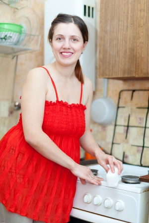 Happy young woman in red cleans gas stove with melamine sponge in kitchen at home photo