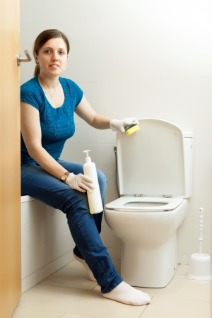 woman cleaning toilet bowl with sponge in bathroom photo