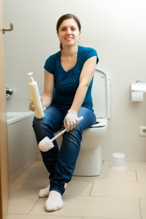 Smiling young woman in bathroom with brush and cleaner Stock Photo - 19523172