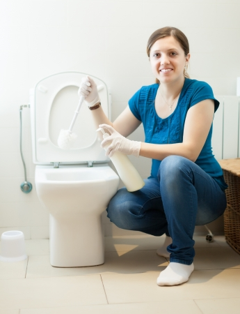 Smiling housewife cleaning toilet bowl with brush in bathroom Stock Photo - 19528338