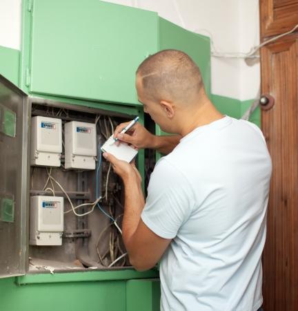 contador electrico: El hombre vuelve a escribir las lecturas de medidor el�ctrico en la casa