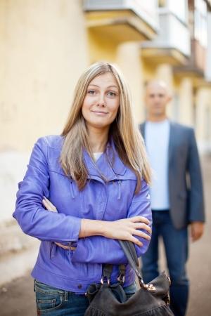 molestation: Man walks behind woman on the city street Stock Photo