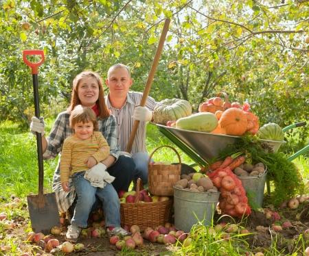 schubkarre: Gl�ckliche Eltern und Kind mit geerntetem Gem�se im Garten