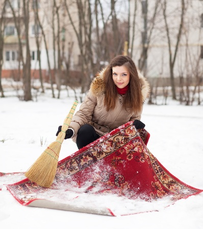 Smiling girl cleans carpet with snow in winter day outdoor photo
