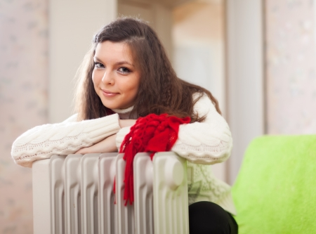 calorifer: Long-haired woman  warms near warm heater  in home