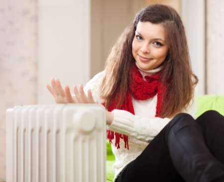 and heating: Smiling woman warms hands near radiator at home
