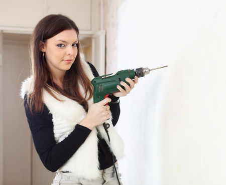 Woman drill hole in the wall with a drill photo
