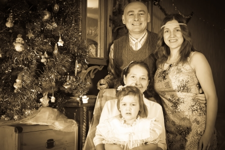 Vintage image of happy  family of three generations celebrating Christmas in living room photo
